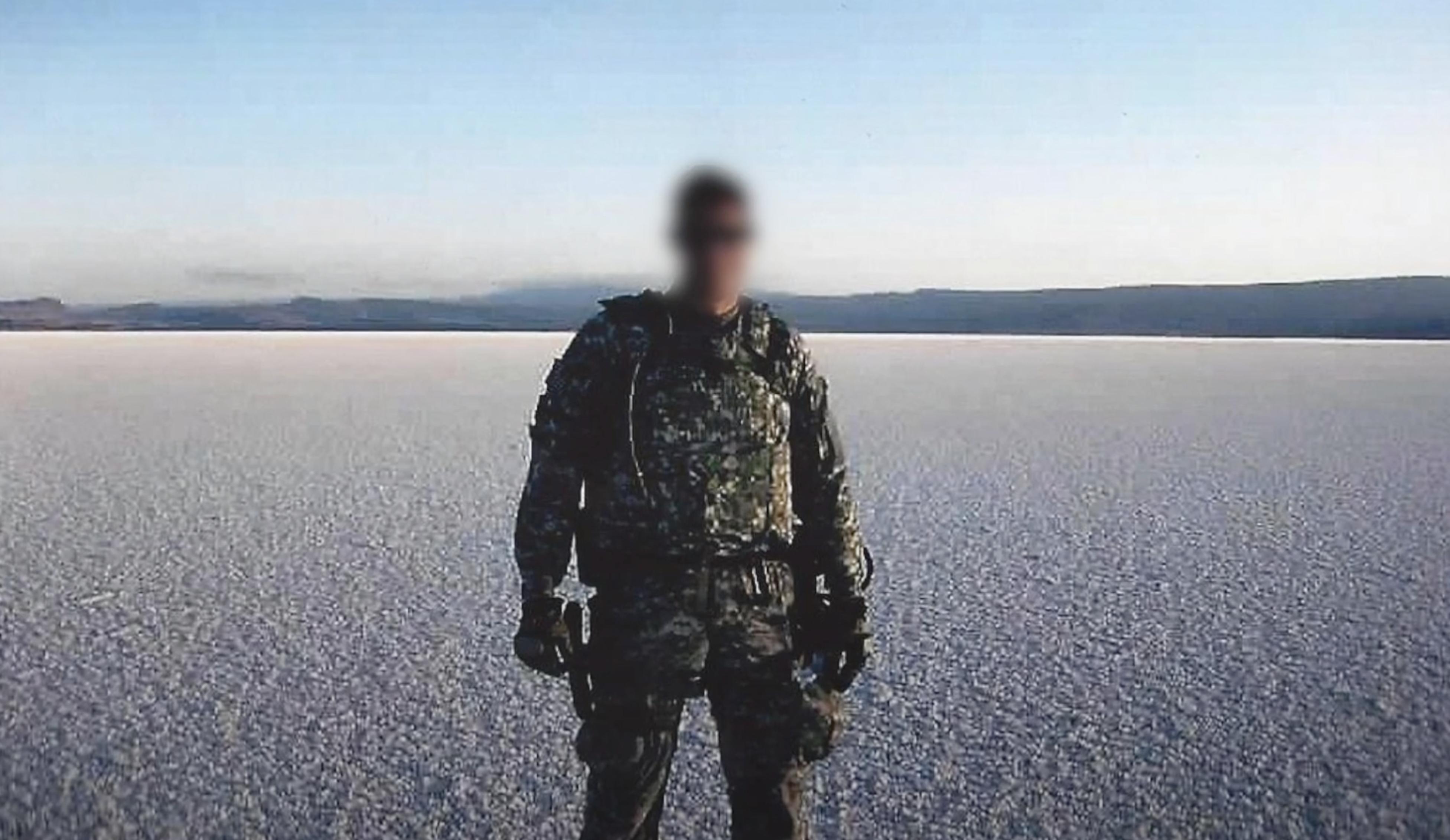 A man stands in U.S. military uniform in a desert scene.
