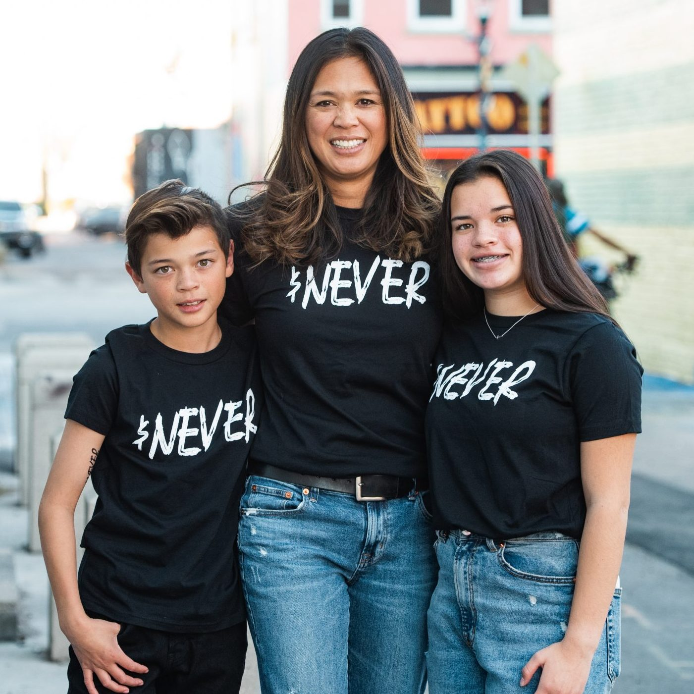 A mom and her two kids stand together on a street in Colorado while wearing The Exodus Road t-shirts.