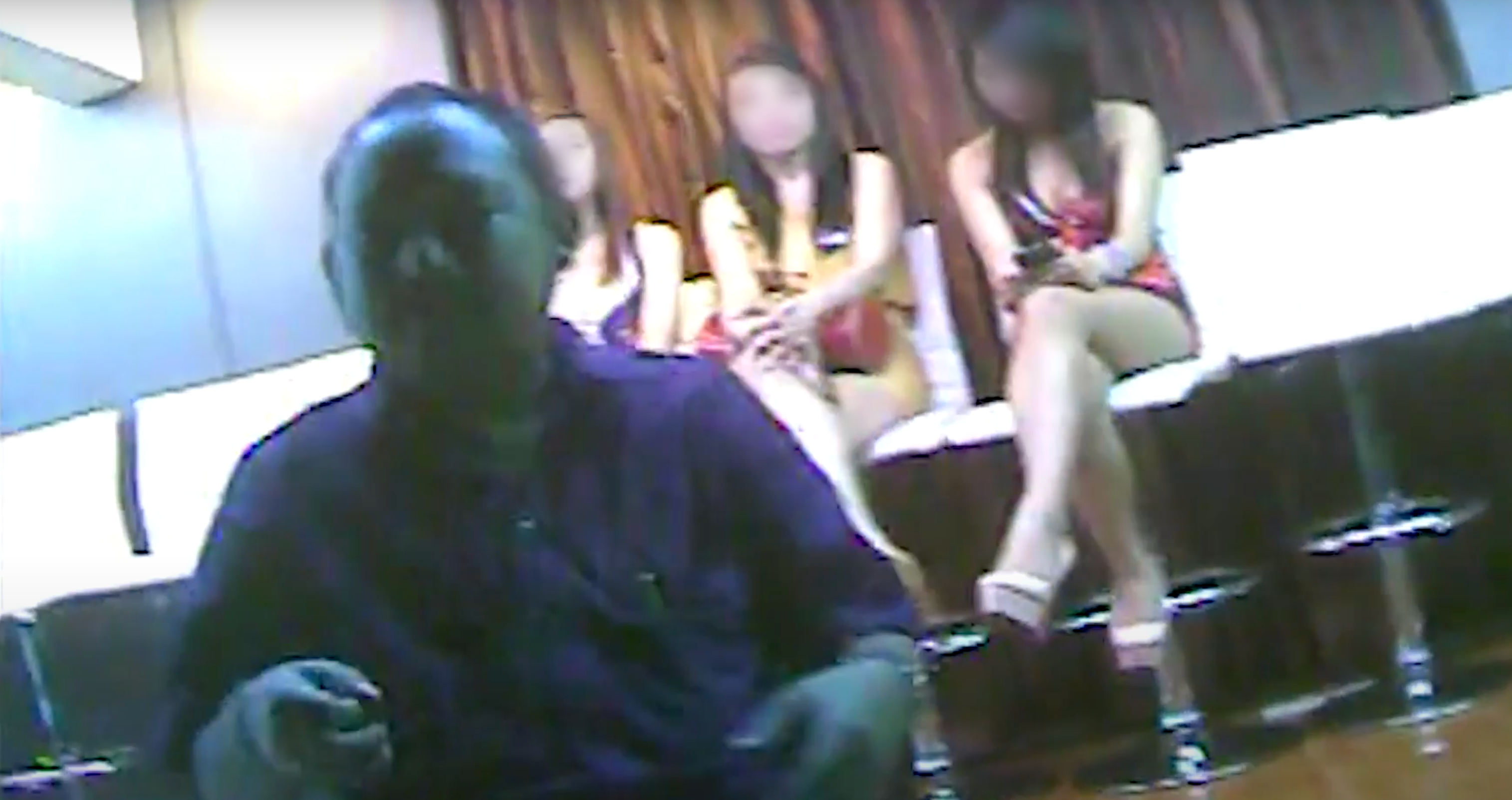 Three female victims of human trafficking sit, legs crossed, behind a male trafficker.