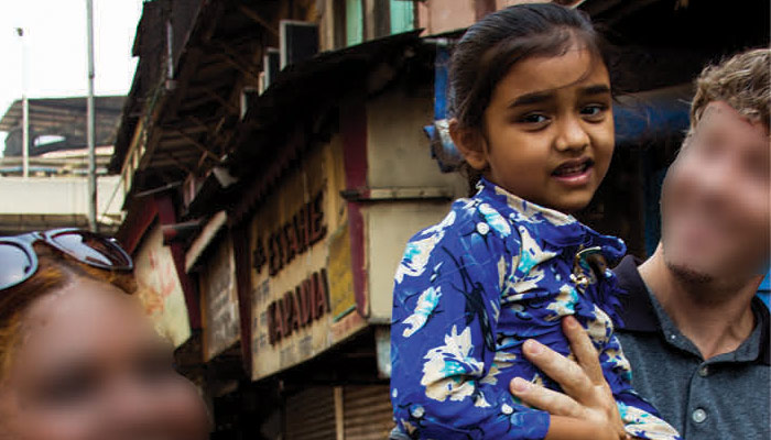 Young girl in India being held by a man on the street.