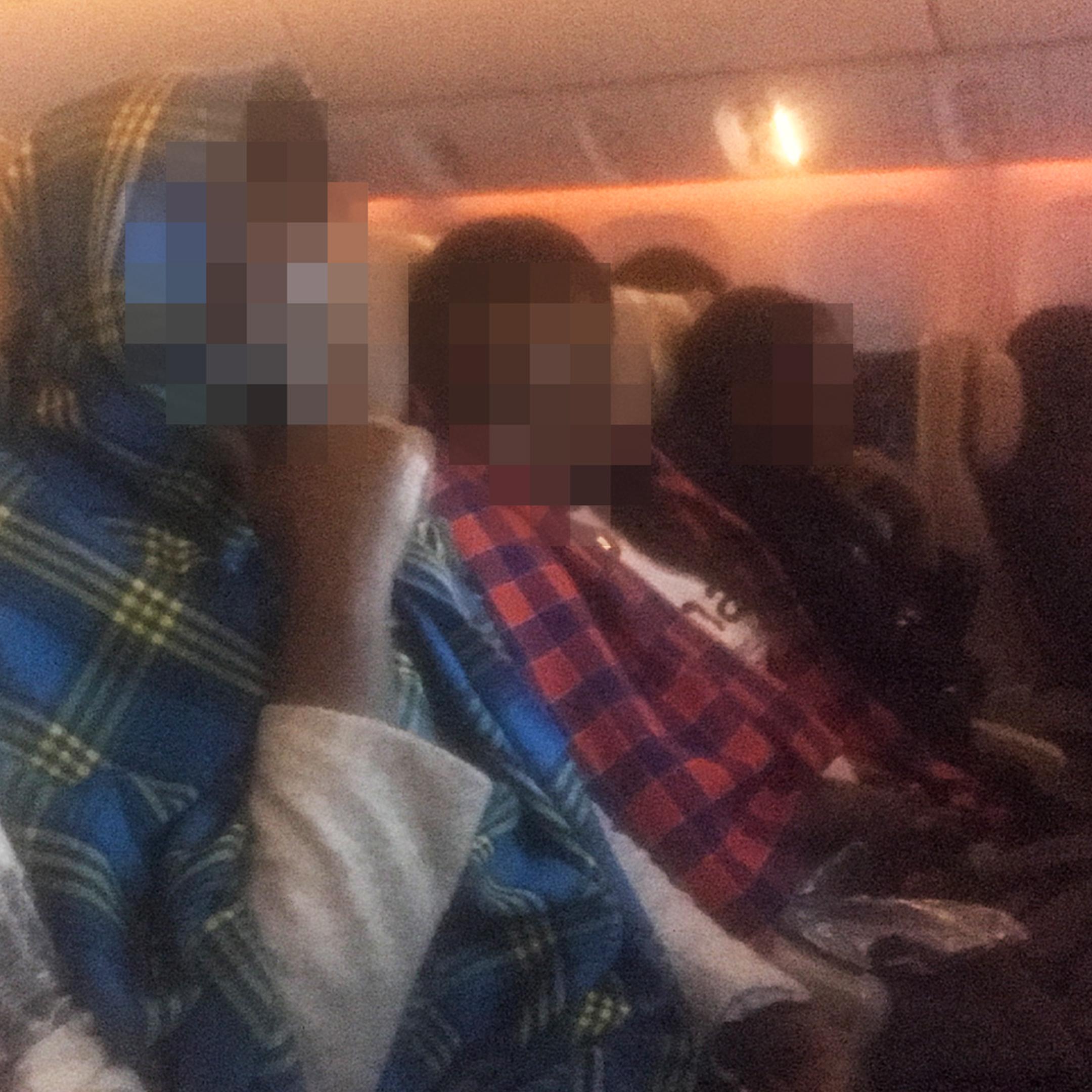 Real image of Kenyan women traveling to Saudi Arabia on an airplane.
