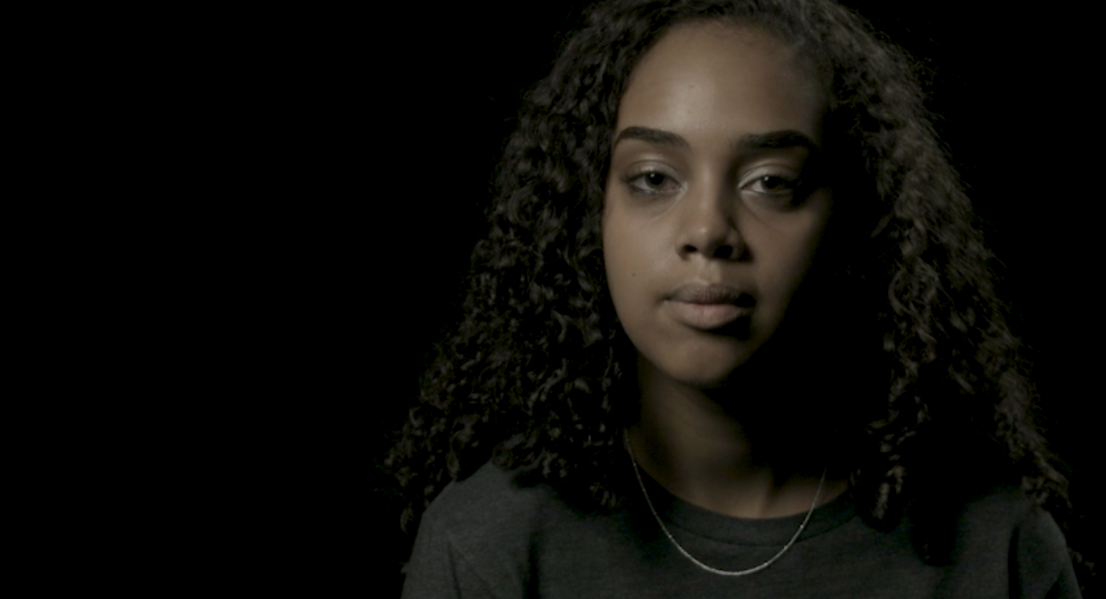 """Thumbnail preview image for """"She Could Be Me"""" video, featuring a 15-year-old African American girl smiling at the camera."""