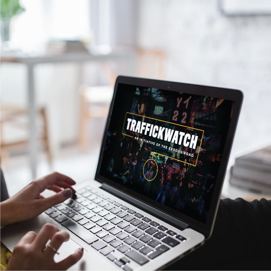 Woman navigates to TraffickWatch Academy webpage on a laptop computer.