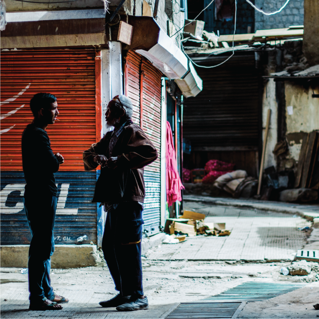 Representative image of national investigator speaking to man in a street alley in southeast Asia.