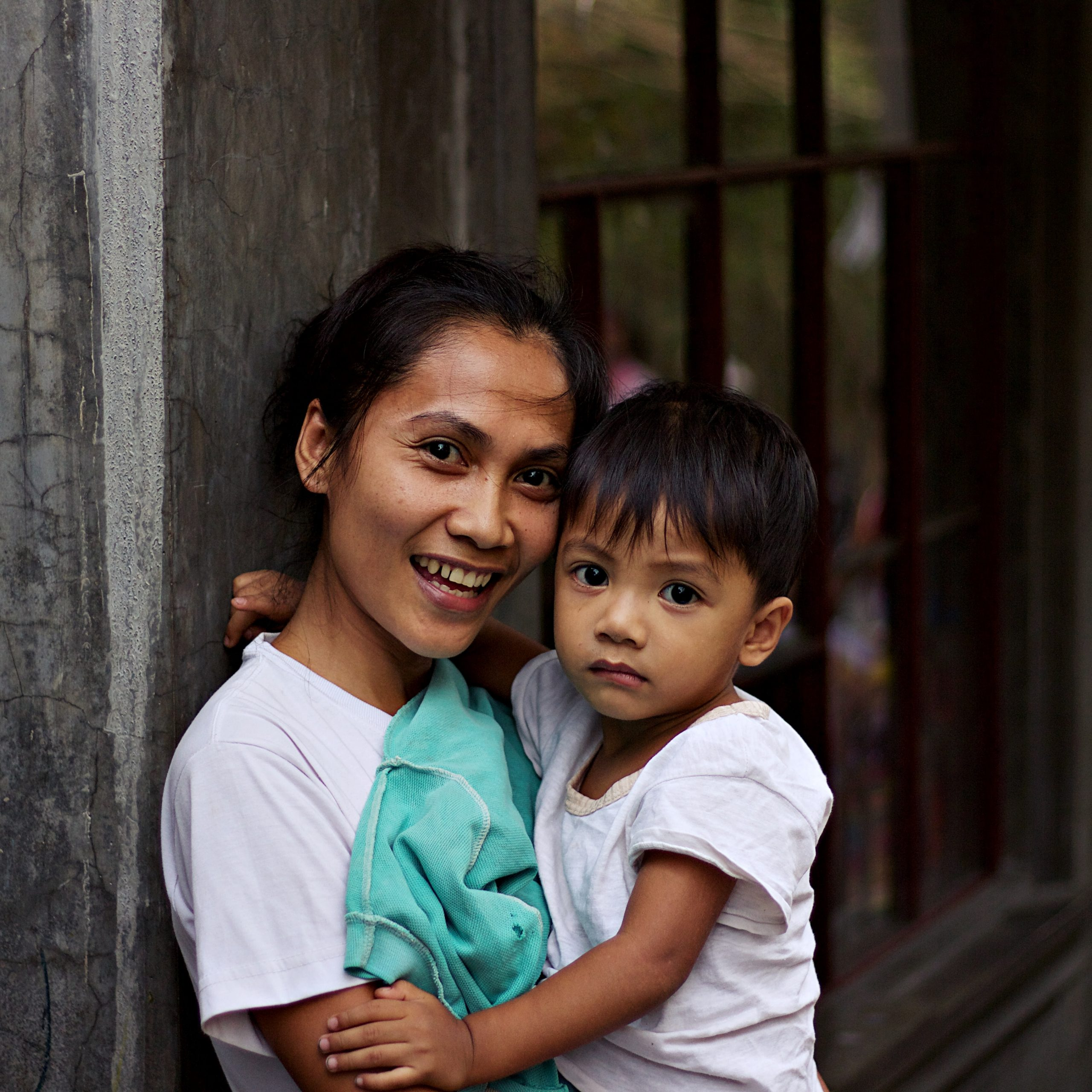 Representative image of young, cheerful, southeast Asian female survivor holding her 3 year old son.