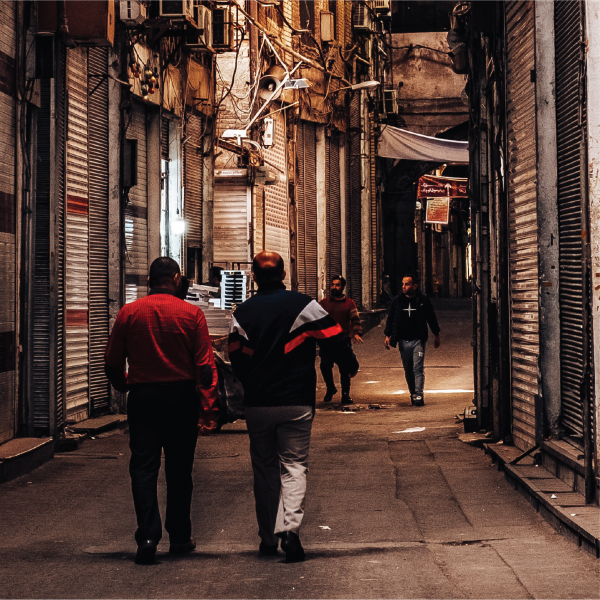 Representative image of two operatives walking together down a dark alley in a Latin American street.