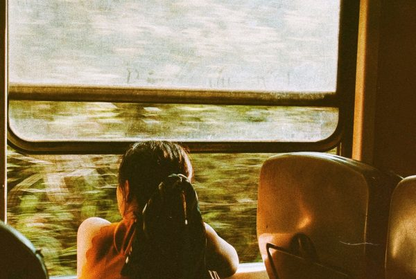 Young female Thai survivor sits looking out the window of a train.